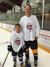 Youth hockey player with dad on the ice